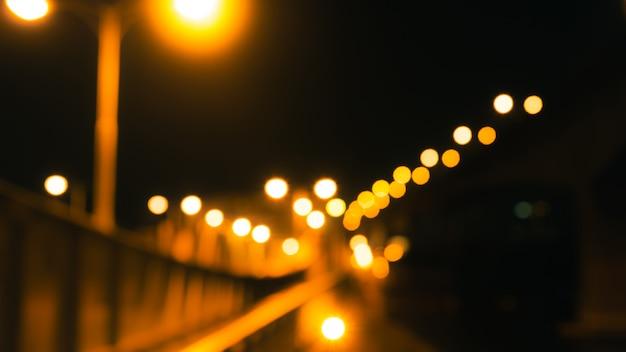 Pont flou, route et poteau électrique avec jaune floue dans la nuit. concept de la vie nocturne. bokeh de lumières or et orange dans la rue