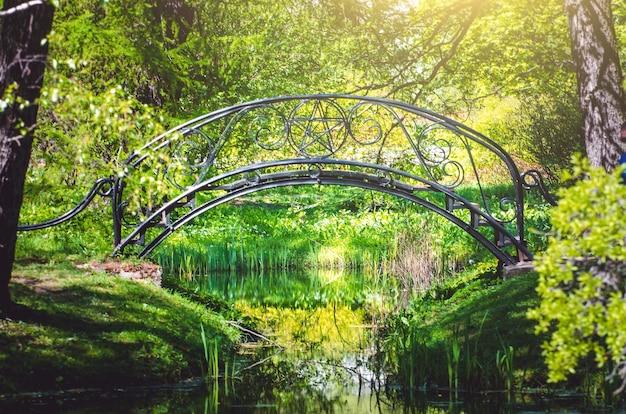 Pont forgé en métal noir au-dessus de la rivière dans le parc.