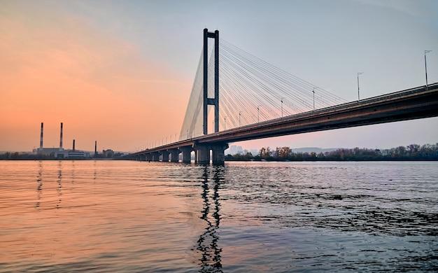 Pont à haubans à un pylône sur la rivière de la ville au coucher du soleil.