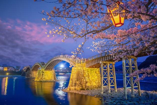 Pont kintaikyo à iwakuni, japon au coucher du soleil avec des fleurs de cerisier