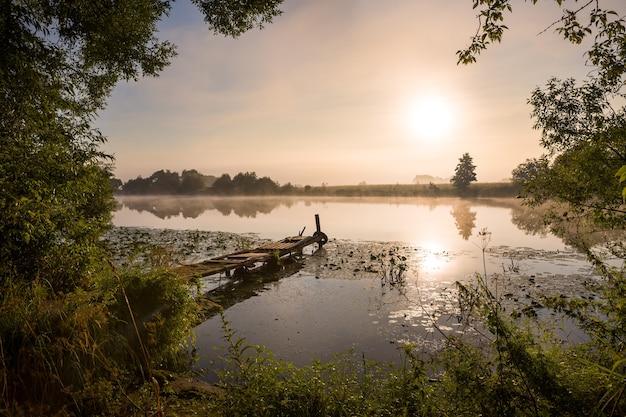 Pont de pêche pour bateau et paysage calme du lever du soleil matinal avec brouillard sur la rivière