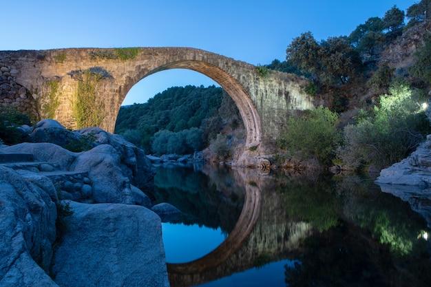 Pont de pierre sur une rivière la nuit