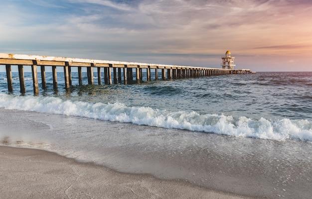 Pont piétonnier en ciment sur la plage jusqu'à la mer.