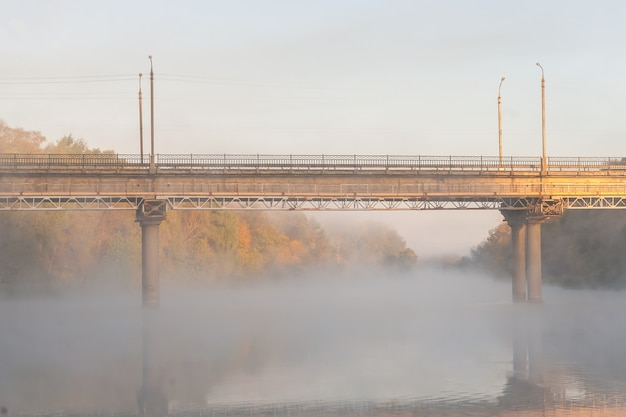 Pont sur la rivière couverte de brume d'automne