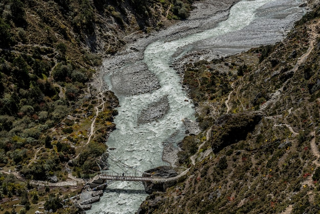 Pont et rivière avec une personne se croisent dans la région de l'everest au népal.