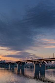 Pont sur la rivière yenisei coucher du soleil du soir. krasnoyarsk, russie. verticale