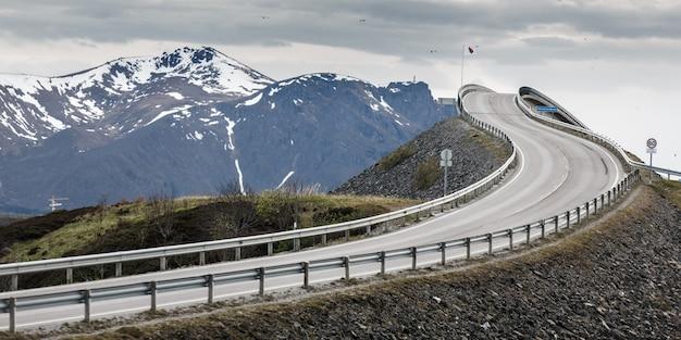Le pont sur la route de l'océan atlantique avec la chaîne de montagnes du bonnet de la neige en norvège