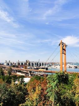 Pont routier, chemin de fer sur le port maritime, fond de port avec ascenseurs de grenier, yachts, navires, grues flottantes dans le port.
