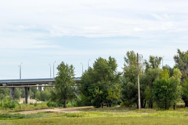 Pont routier traversant un champ avec des arbres et des buissons. panorama.