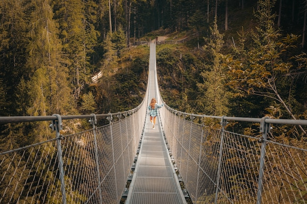 Pont suspendu blanc et marron entouré d'arbres verts pendant la journée