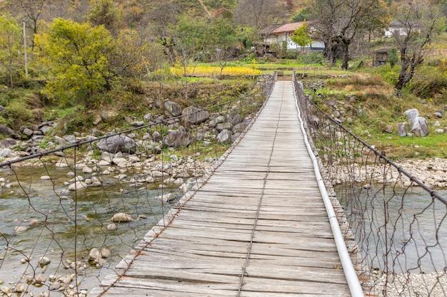 Pont suspendu en bois sur une rivière en montagne