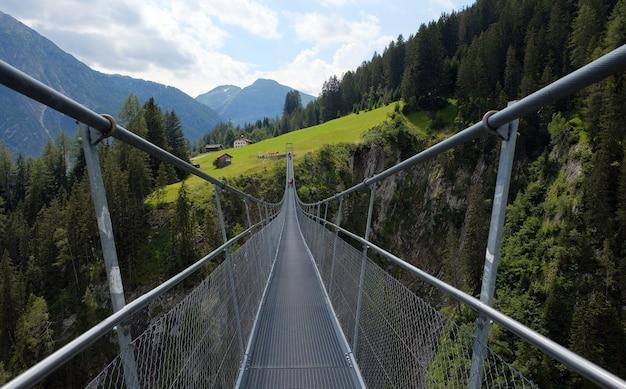 Pont suspendu haut entre les montagnes, les arbres et les rochers à lechtal, lech, autriche