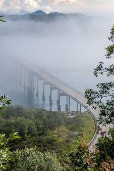 Le pont de tjeldsund dans le brouillard. le pont relie l'île hinnoya au continent, la norvège