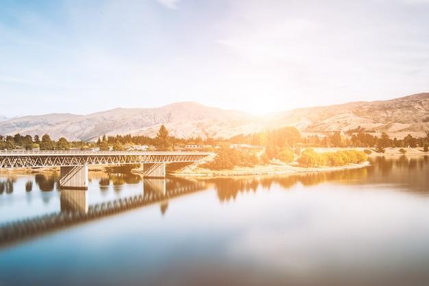 Pont traversant un lac au coucher du soleil
