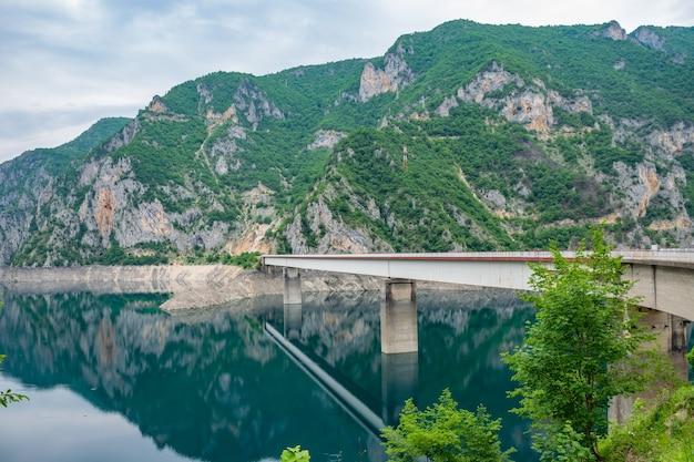 Pont traversant un lac avec des montagnes à l'arrière.