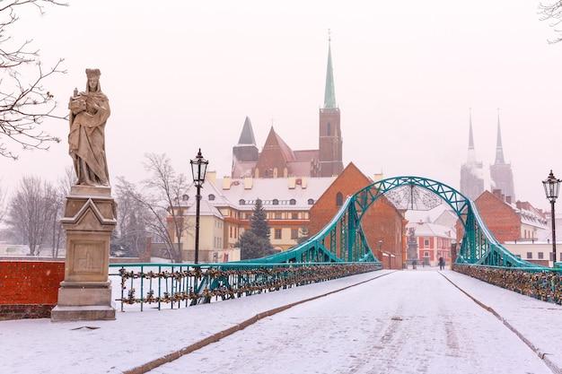 Pont tumski et l'île avec la cathédrale de saint-jean et l'église de la sainte croix et saint-barthélemy dans la journée d'hiver couvert de neige à wroclaw