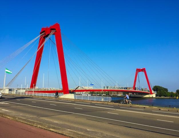 Pont de willemsbrug enjambant la rivière nieuwe maas à rotterdam, pays-bas, pylônes du pont rouge et