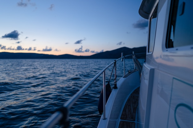 Pont de yacht blanc naviguant en pleine mer au coucher du soleil