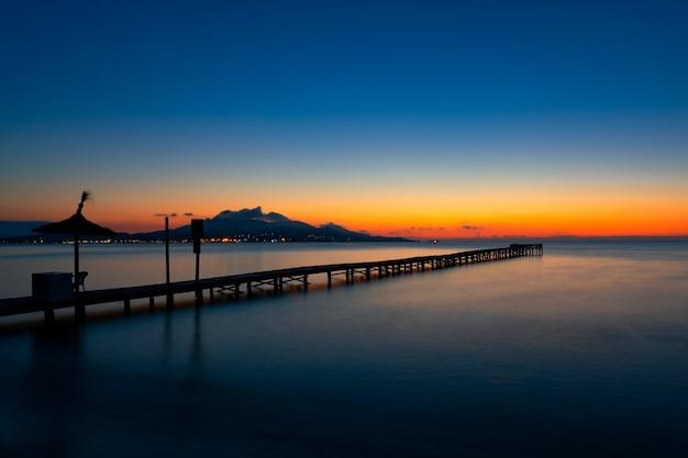 Ponton au lever du soleil sur playa de muro, majorque, sapin