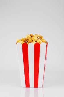 Pop corn au sirop de caramel dans la boîte en carton posée sur la table