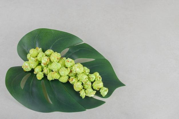 Pop-corn confit vert empilé sur une feuille décorative sur table en marbre.