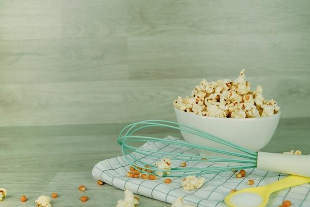 Pop-corn dans un bol blanc avec une cuillère pastel, du sel, un batteur à main et des graines de maïs sur fond de bois.