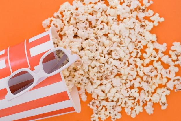 Pop-corn dans un bol en papier et des lunettes 3d pour regarder un film sur fond orange, vue de dessus.