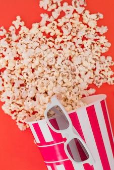 Pop-corn dans un bol en papier et des lunettes 3d pour regarder un film sur fond rouge, vue de dessus.