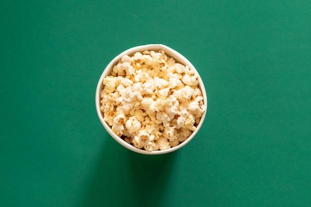 Pop-corn dans un sac en papier sur l'espace de copie vue de dessus fond vert.