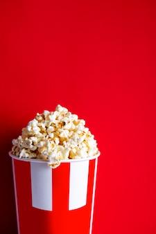 Pop-corn dans un verre sur fond rouge. maïs soufflé au caramel salé avec bacon et fromage. aller au cinéma. les collations sont délicieuses dans un verre. lieu de fond rouge pour la rédaction. candy à kina.