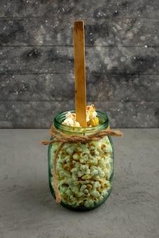Pop-corn lumineux salé à l'intérieur de la boîte de verre sur un gris