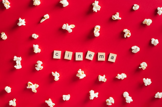 Pop-corn plat sur fond rouge avec lettrage de cinéma