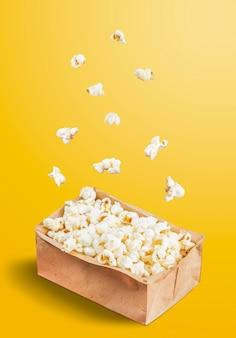 Pop-corn tombant dans un pot sur fond jaune. fête de juin.
