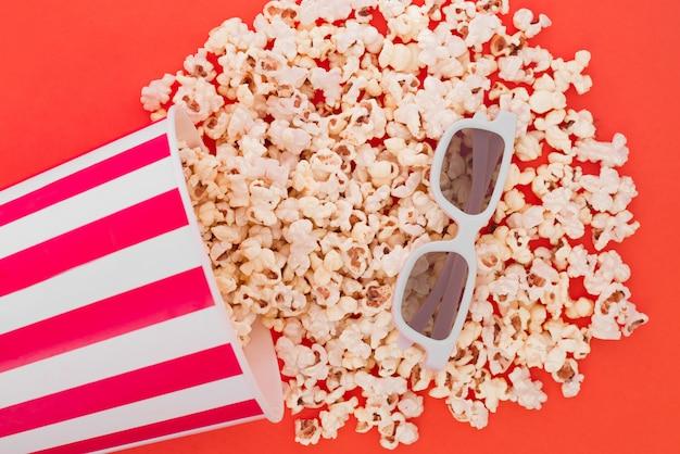 Pop-corn versant d'un bol en papier sur un fond rouge, et des lunettes 3d pour regarder le film, une vue de dessus