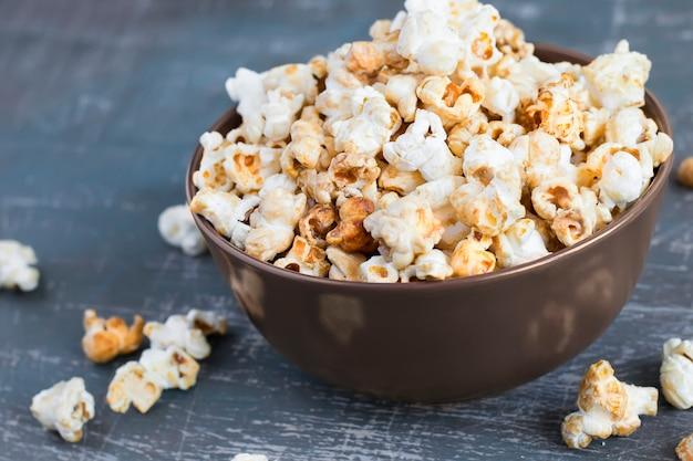Popcorn au caramel sucré dans un bol sur un fond bleu foncé