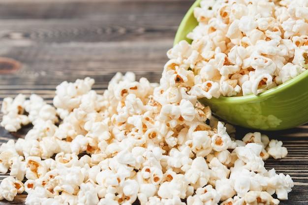 Popcorn au caramel sucré dans un bol vert sur fond en bois