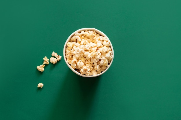 Popcorn dans un sac en papier sur fond vert. concept de régime malsain.