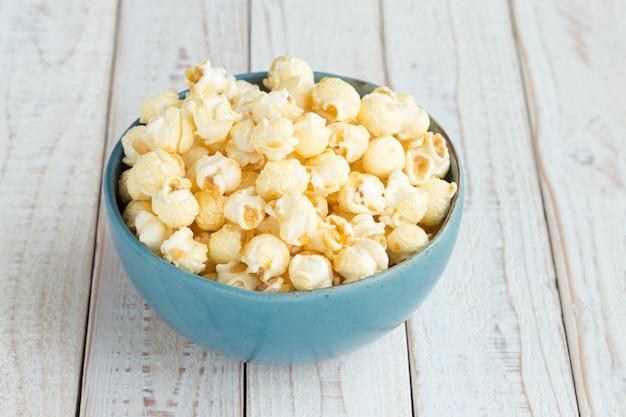 Popcorn dans une tasse bleue sur une table en bois blanc