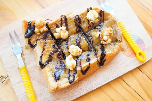 Popcorn garnie de pain au chocolat toasté sur une table en bois