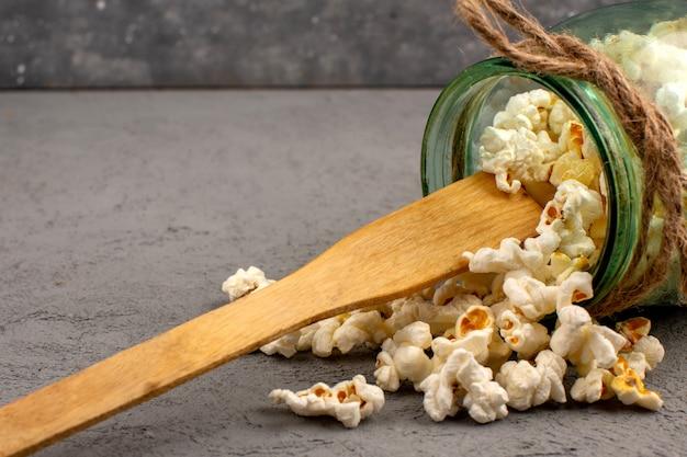 Popcorn lumineux salé délicieux à l'intérieur de la boîte de verre sur un sol gris