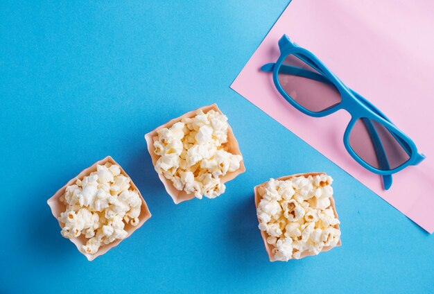 Popcorn avec des lunettes 3d sur bleu
