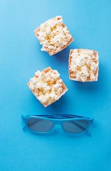 Popcorn avec des lunettes 3d sur fond bleu
