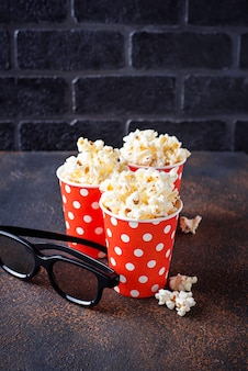 Popcorn avec des lunettes 3d sur fond sombre