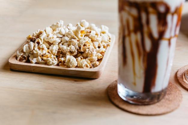 Popcorn salé servi dans une assiette en bois sur une table carrée en bois.