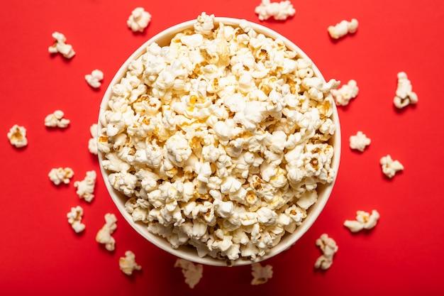 Popcorn savoureux dans une tasse en papier sur fond rouge, vue du dessus