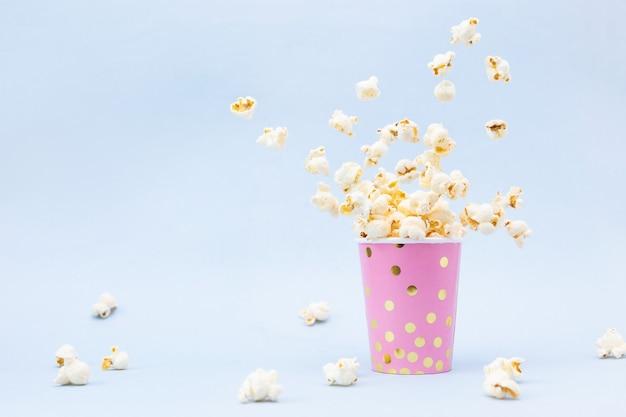Popcorn volant dans un verre brillant et sur bleu
