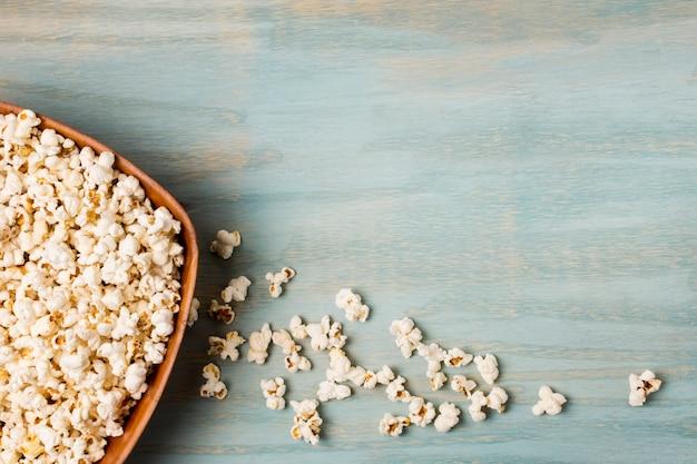 Popcorns renversé du bol sur le bureau bleu