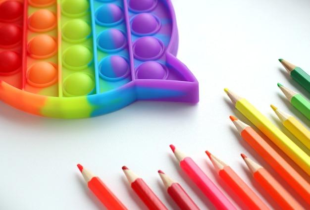 Popit jouet antistress multicolore avec des crayons de couleur sur fond blanc