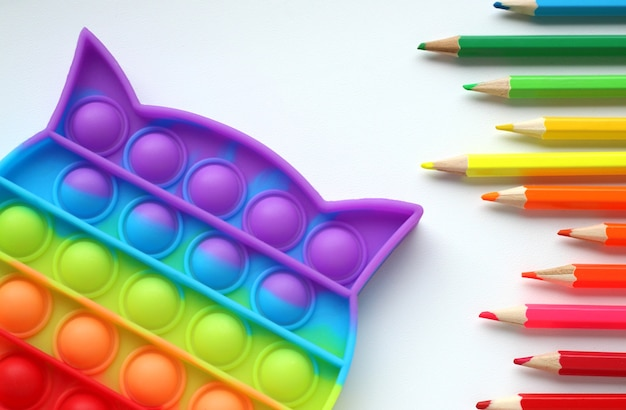 Popit jouet de couleur antistress avec des crayons de couleur sur fond clair