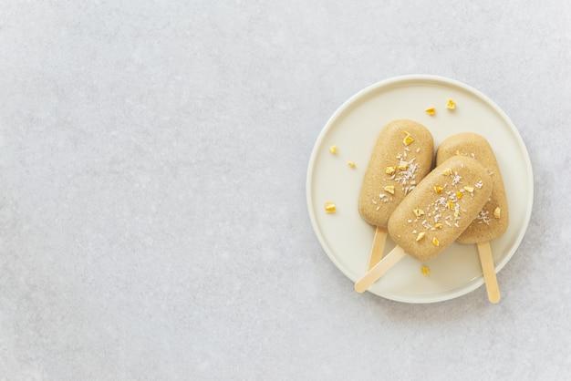 Popsicle au chocolat noix de cajou morceaux de mangue et noix de coco sur une assiette